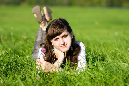 pretty girl lying in grass with flower Stock Photo - 7065157