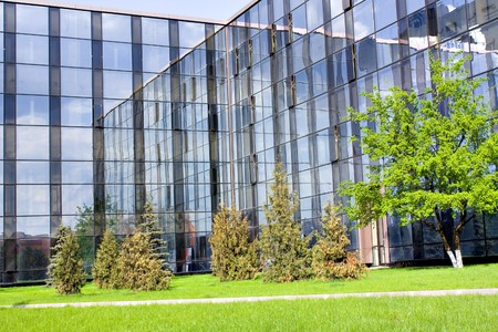 glass buildings and blooming apple trees garden in spring Stock Photo
