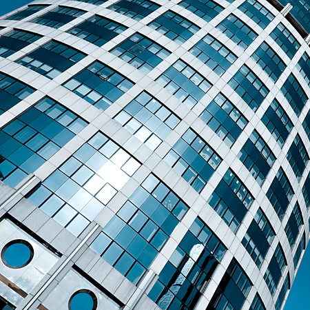 textured tower skyscraper with reflection of blue cloudless sky photo