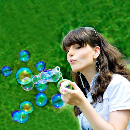 Young girl blowing soap bubbles in summer green park photo