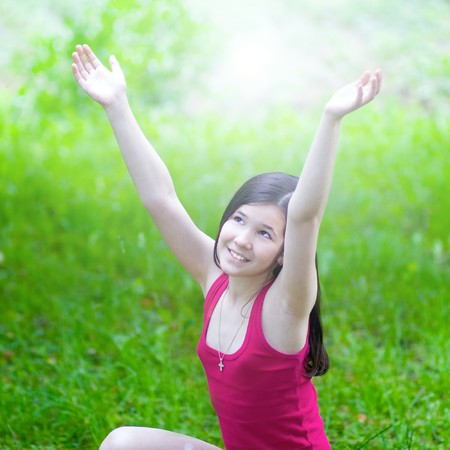 beauty girl with open hands over green grass in sunny day photo