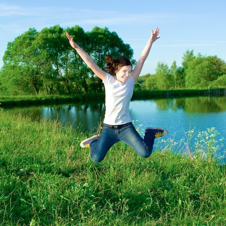 smiling jumping girl with open hands Stock Photo