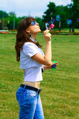 whiff: Young girl blowing soap bubbles in autumn park