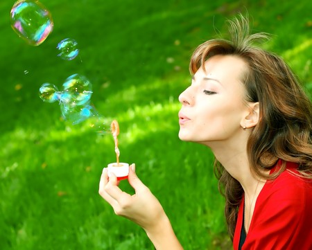Young girl blowing soap bubbles photo