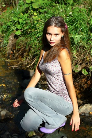 attractive woman sitting on the stones in the river Stock Photo - 7956606