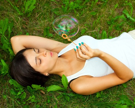 Young girl laying and inflating soap bubbles photo
