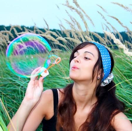 Junge Mädchen bläst eine große Seifenblase