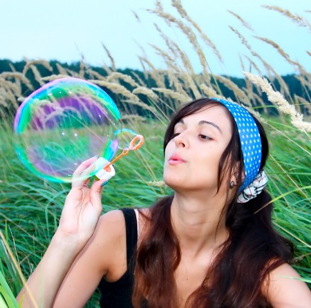 breath: Young girl blowing a big soap bubble Stock Photo