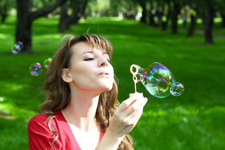 young attractive girl inflating soap bubbles in spring park photo