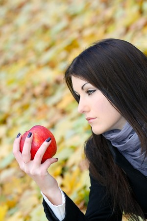 portrait of the beauty girl with red color apple in park photo