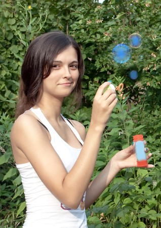 attractive girl blowing soap bubbles photo