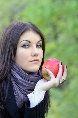 portrait of the gorgeous woman with bright fresh red apple photo