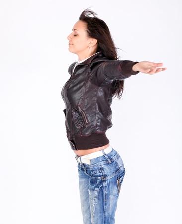 jeans apretados: mujer seductora en la chaqueta de cuero y pantalones vaqueros permanente con las manos abiertas