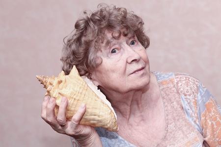 great grandmother: Sonriente bisabuela escuchar una concha