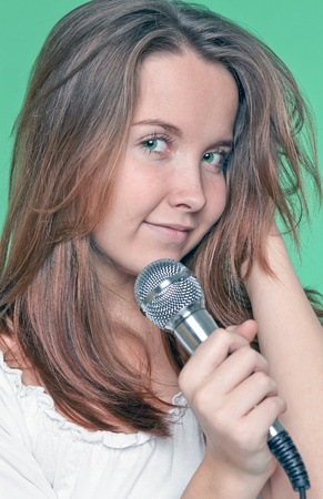 portrait of beautiful singer girl with microphone in hand photo