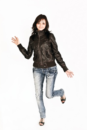 pretty slim girl dancing in trendy jeans and leather jacket photo