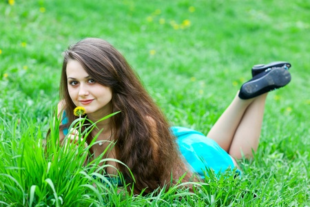 portrait of attractive young girl with dandelion relaxing on the lawn photo