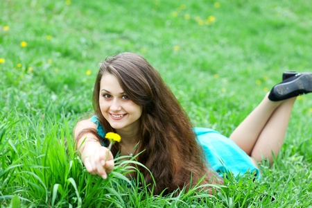 beautiful girl with dandelion relaxing on the lawn photo
