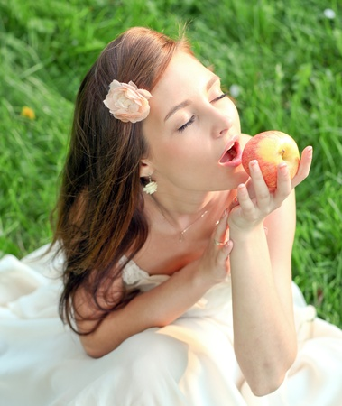 ambrosia: brunette young girl with an apple in summer park enjoying Stock Photo