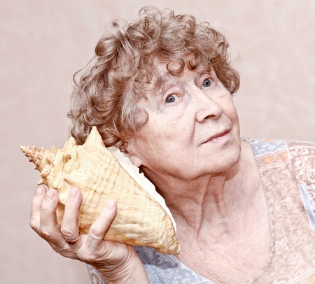 new age music: Smiling great grandmother listening to a seashell