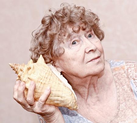 great grandmother: Sonriendo bisabuela escuchando una concha marina