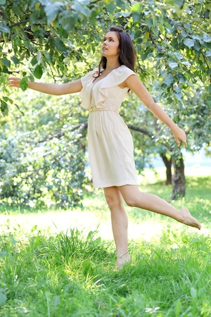 sundress: Beautiful young woman dancing in the morning bright summer orchard