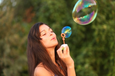 inflating: Pretty woman inflating soap-bubbles