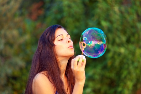 portrait of attractive young girl inflating colorful soap bubbles outdoor photo