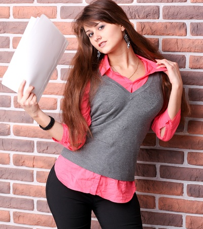 sexy office girl: Smiling young business woman with document over brickwall Stock Photo