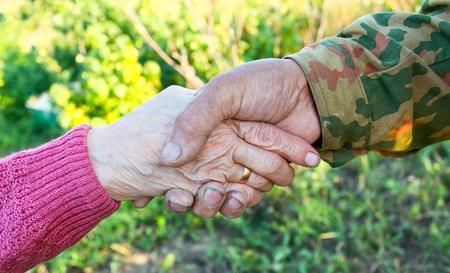 handclasp: handclasp between elderly people outdoor Stock Photo