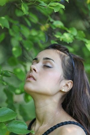 sensual portrait of young lady enjoying in summer park photo