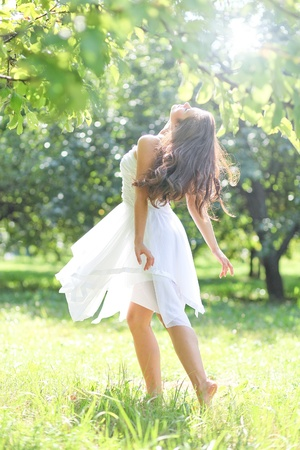 adorable young girl in white clothes enjoying barefooted over morning dew of summer park photo