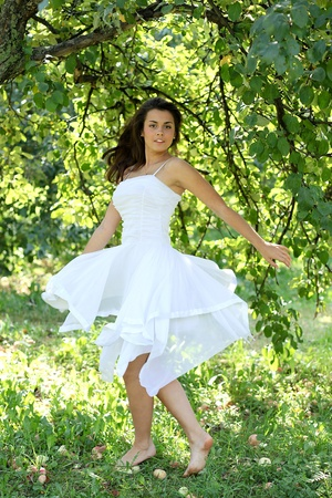 tooth fairy: Beautiful young woman dancing in the morning bright summer orchard