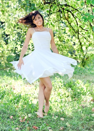 Beautiful young woman dancing in the morning bright summer orchard Stock Photo - 10980691