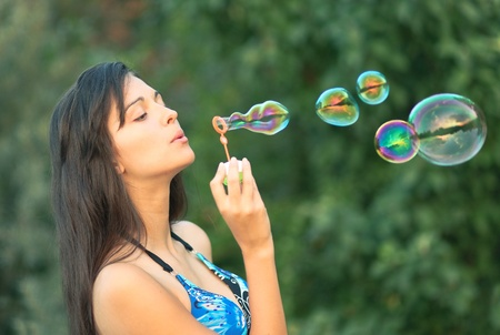 gentle dream vacation: portrait of attractive young girl inflating colorful soap bubbles in nature