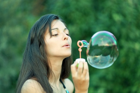 inflating: portrait of attractive young girl inflating colorful soap bubbles in nature