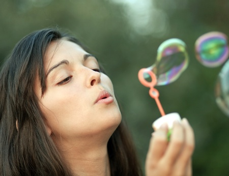 inflating: Pretty woman inflating soap-bubbles Stock Photo