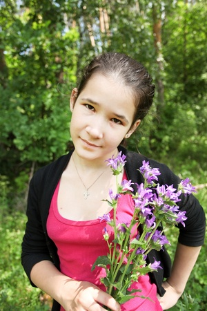 Happy young girl with brigth bluebell flowers in beautiful bunch outdoor photo