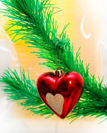 Red heart hanging on Christmas fir tree photo