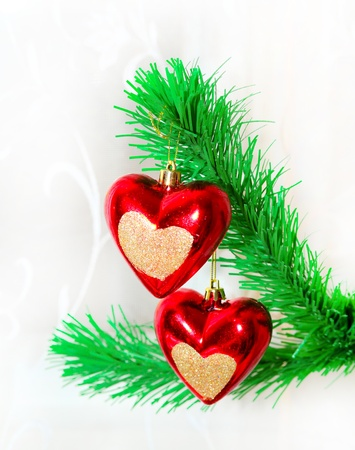 Red hearts hanging on Christmas fir tree photo