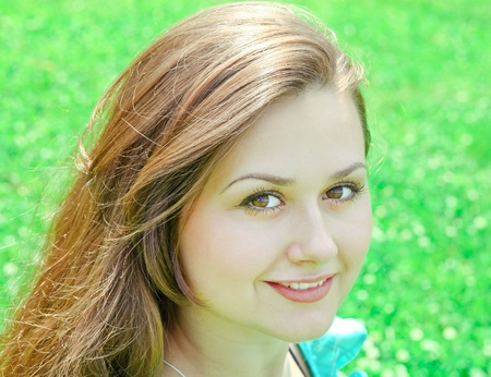 portrait of beautiful young woman relaxing in summer park photo