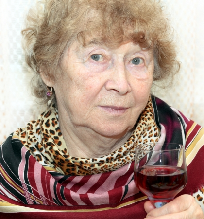 Attractive elegant senior lady holding a glass of red wine on a toast photo