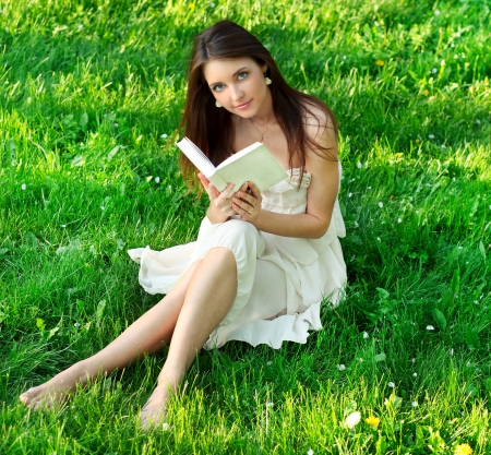 nude girl sitting: Beautiful girl reading a book outside