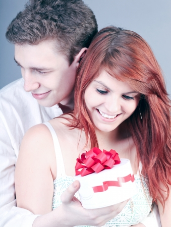 Lovely couple surprising with red gift box photo