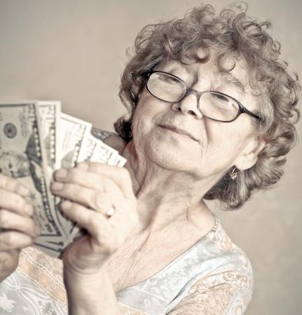 Senior glückliche Frau mit Geld Standard-Bild