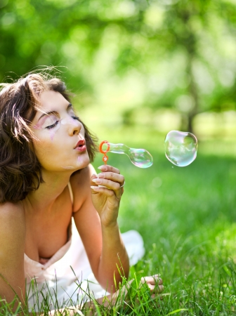 inflating: romantic young girl laying and inflating colorful soap bubbles in spring park Stock Photo