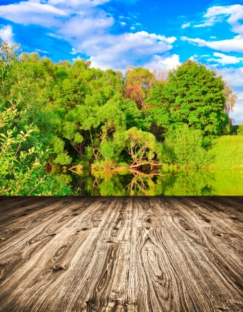 Light picturesque scene of beautiful rural lake in sunny summer park over blue sky with first dawn rays on the wall inside room interior with frame textured wooden brown panel floor background
