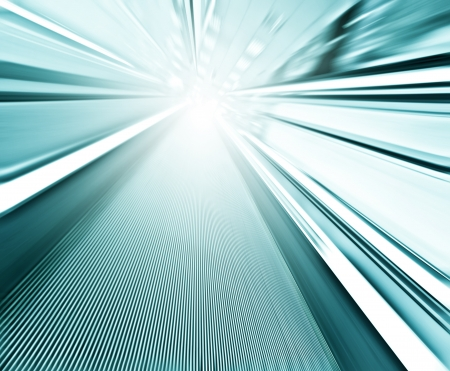 Perspective wide angle view of modern light blue illuminated and spacious high-speed moving commercial escalator with fast blurred trail of handrail in vanishing traffic motion in airport corridor Stock Photo