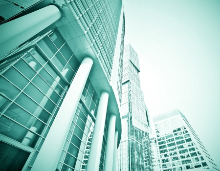 Panoramic and perspective wide angle view to steel blue background of glass high rise building skyscrapers in modern futuristic downtown at night Business concept of successful industrial architecture Stock Photo