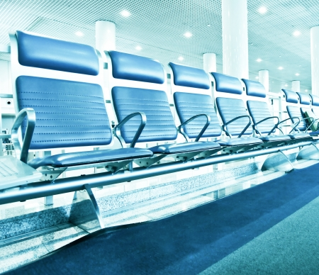 Business and transportation background of contemporary blue spacious hallway of airport, waiting room with seats